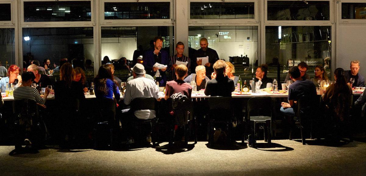 image für website von cratedesign_dem event mobiliar zum mieten aus ungelabelten getraenkekisten aus berlin_mit der beschriftung_img-cratedesign-offen-galerie-dinnerperformance_tisch_gäste_landscape_innen